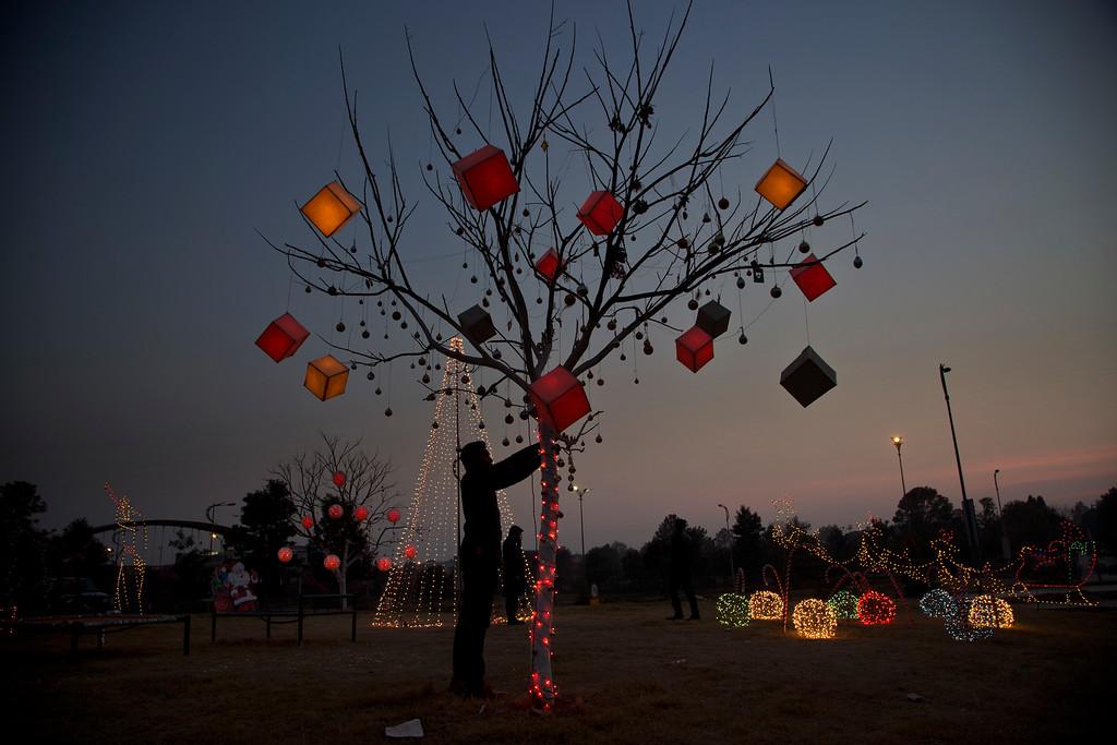 . A Pakistani decorates a tree in a Christian neighbourhood of Rawalpindi, Pakistan, to celebrate Christmas, Sunday, Dec. 25, 2016. (AP Photo/B.K. Bangash)