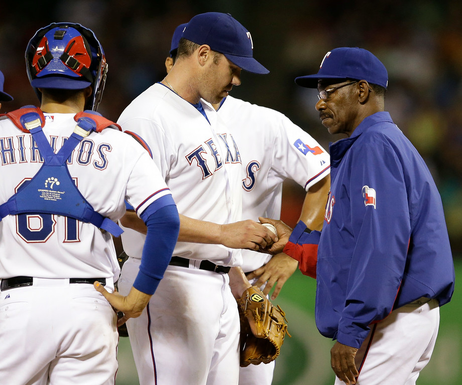 . Texas Rangers\' Colby Lewis hands the ball over to manager Ron Washington as catcher Robinson Chirinos watches in the seventh inning of a baseball game against the Detroit Tigers, Tuesday, June 24, 2014, in Arlington, Texas. The Tigers won 8-2. (AP Photo/Tony Gutierrez)