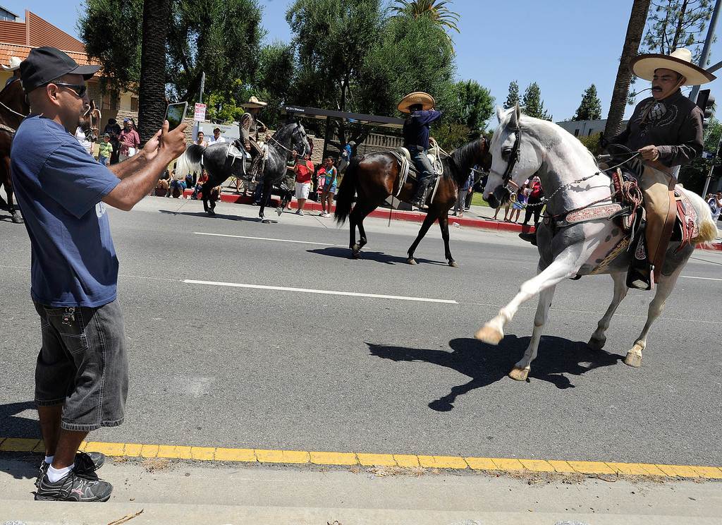 . Rosendo Lopez Jr. takes photos of his father during the parade. The Annual Canoga Park Memorial Day Parade marched down Sherman Way from Owensmouth east to Mason Street where it concluded at the First Baptist Church. Canoga park, CA 5/27/2013(John McCoy/LA Daily News)