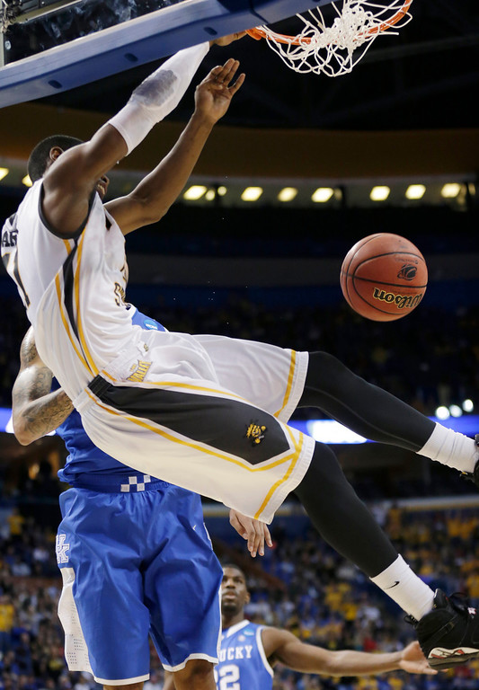 . Wichita State forward Cleanthony Early (11) dunks over Kentucky forward Willie Cauley-Stein (15) during the first half of a third-round game of the NCAA college basketball tournament Sunday, March 23, 2014, in St. Louis. (AP Photo/Charlie Riedel)