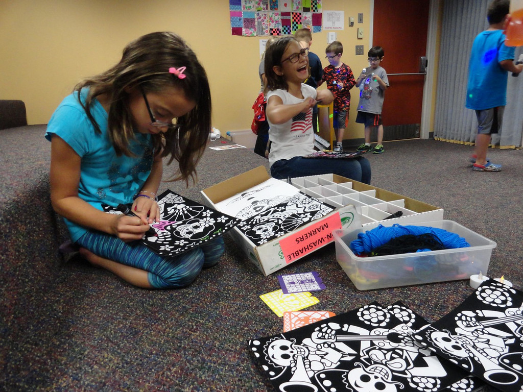 . Sarah and Mary Thacker laugh as they color skeletons during Studio MPL�s celebration of the Day of the Dead. (Courtesy Mentor Public Library)