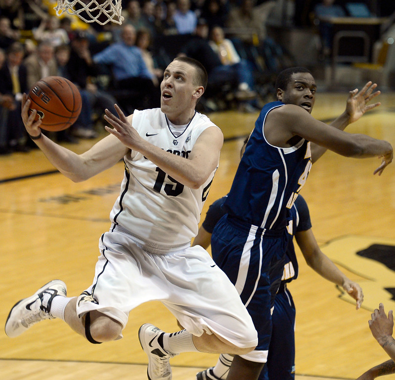 . University of Colorado\'s Shane Harris-Tunks goes for a layup over Ephraim Ekanem during a game against Northern Arizona on Friday, Dec. 21, at the Coors Event Center on the CU campus in Boulder.  (Jeremy Papasso/Daily Camera)