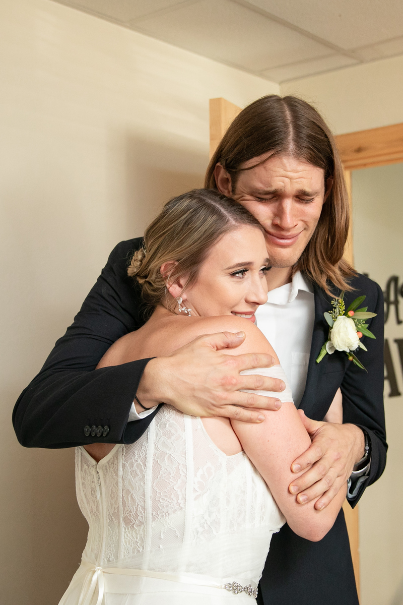 bride hugging her brother just before her wedding ceremony