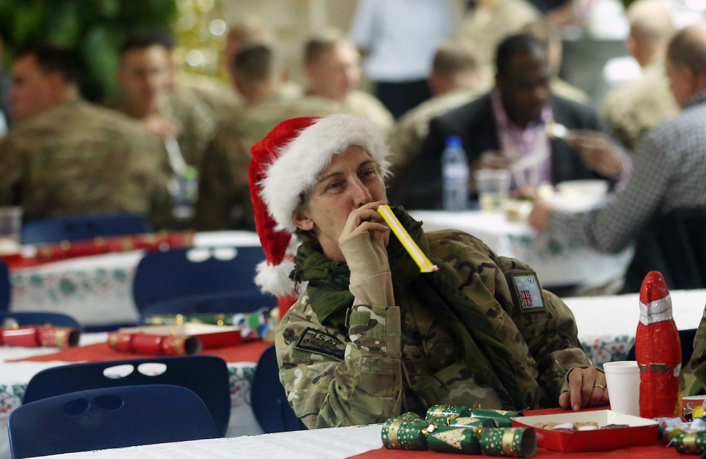 . A NATO service member blows a noisemaker during Christmas celebrations at ISAF headquarter in Kabul, Afghanistan on Thursday, Dec. 25, 2014. U.S. senator John McCain is in Kabul for Christmas day. The former presidential candidate met with Afghan president Ashraf Ghani and his chief executive officer Abdullah Abdullah in separate meetings during his visit on Thursday. (AP Photo/Massoud Hossaini)