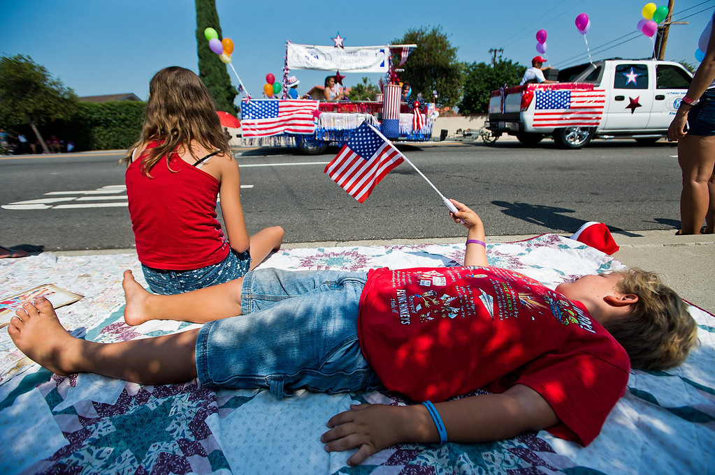 . Jacob Donoghue, 6, of Buena Park, lays on sidewalk as I Love America parade rolls down Stimson Avenue in Hacienda Heights on Thursday, July 4, 2013. (SGVN/Staff photo by Watchara Phomicinda)