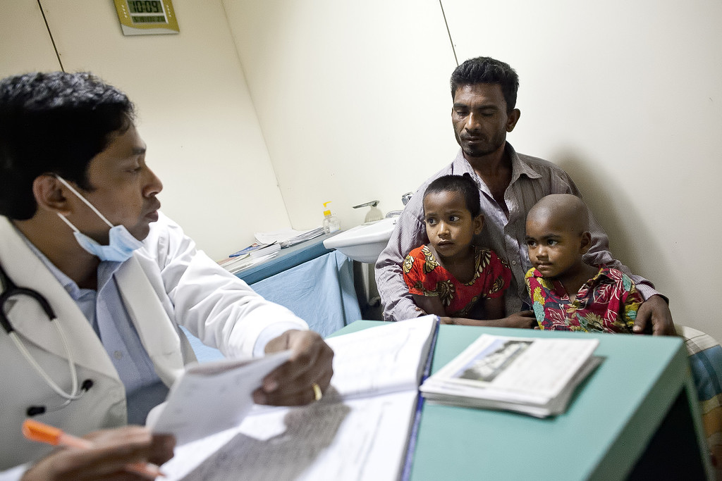 """. A man and his children speak with a doctor at the Emirates Friendship Floating Hospital May 19, 2014 in Chilmari district, Bangladesh. Friendship floating hospitals dock for up to 5 months at remote islands, or \""""chors\"""", in the north of Bangladesh with a full medical team and stocked pharmacy, providing health care at affordable cost.  (Photo by Allison Joyce/Getty Images)"""