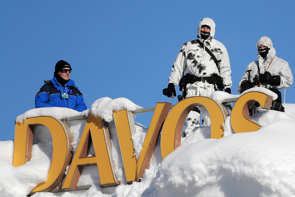 . Armed Swiss police officers stand guard on the roof of a hotel near the congress center where the annual meeting of the World Economic Forum takes place in Davos, Switzerland, Tuesday, Jan. 23, 2018. (AP Photo/Markus Schreiber)