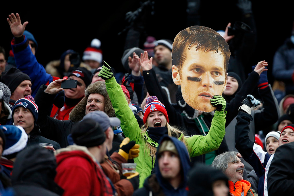 . A fan holds a large photo of New England Patriots quarterback Tom Brady in the first quarter of an NFL football game against the Cleveland Browns, Sunday, Dec. 8, 2013, in Foxborough, Mass. (AP Photo/Elise Amendola)