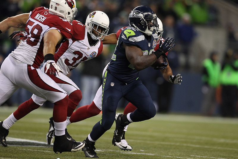 . Robert Turbin #22 of the Seattle Seahawks outruns three Arizona Cardinals defender in the second half at CenturyLink Field on December 9, 2012 in Seattle, Washington.  (Photo by Kevin Casey/Getty Images)