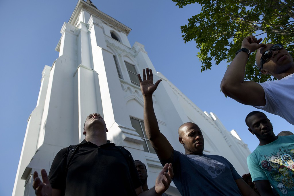 """. People pray outside Emanuel AME Church after the church was reopened on June 20, 2015 in Charleston, South Carolina. A website apparently created by Dylann Roof emerged Saturday in which the accused Charleston church shooter rails against African Americans and appears in photographs with guns and burning the US flag. His arrest warrant revealed how on June 17 he allegedly shot the six women and three men, aged 26 through 87, multiple times with a high-caliber handgun and then stood over a survivor to make a \""""racially inflammatory\"""" statement.     AFP PHOTO/BRENDAN  SMIALOWSKI/AFP/Getty Images"""