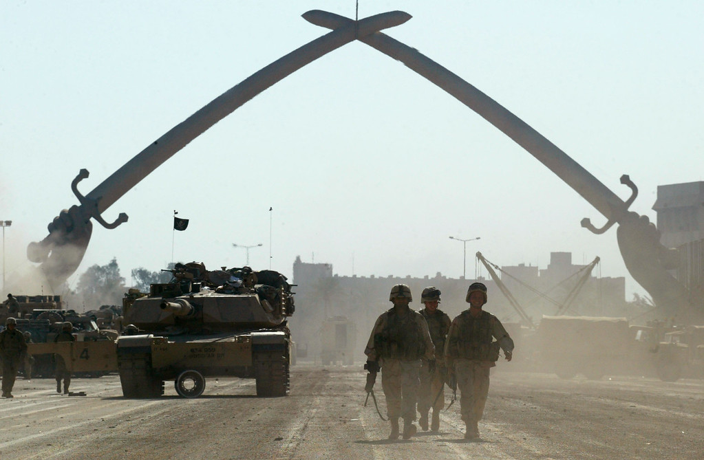 . U.S. Army soldiers walk near a massive arch of swords at Saddam Hussein\'s military parade grounds on Friday, April 11, 2003. (AP Photo/John Moore)