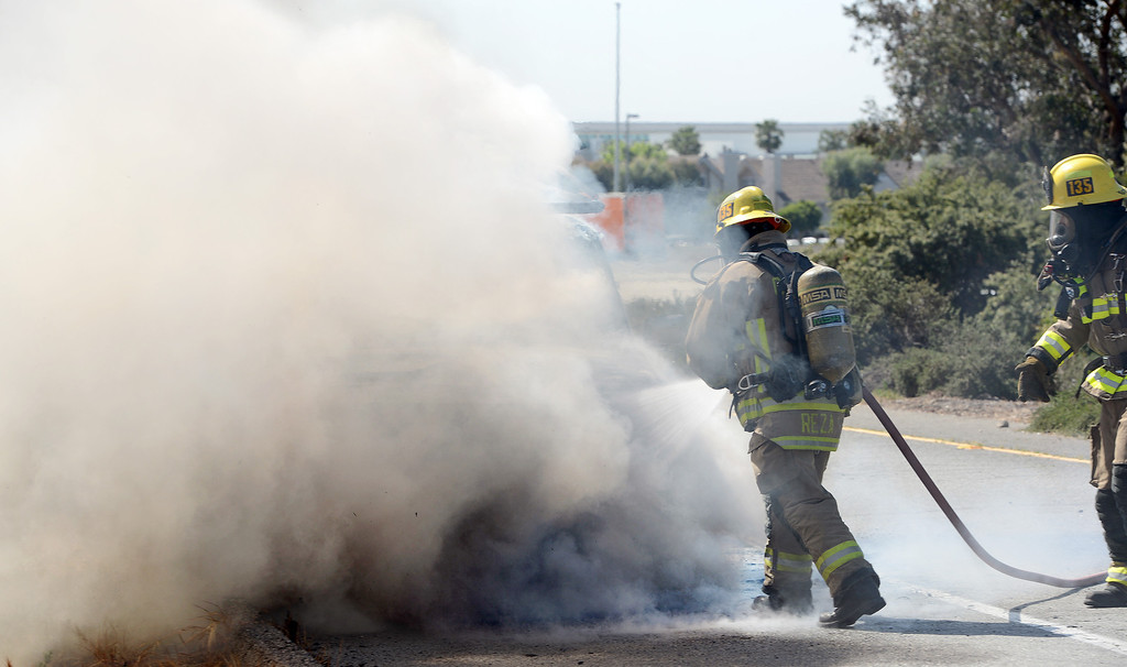 . Ontario firefighters Danny Reza, left, and Tommy Pacheco get water on a vehicle fire on the Vineyard offramp Thursday May 2, 2013. Marco Perez of Riverside said he smelled gas coming from his truck and pulled over to the shoulder of the Vineyard Avenue offramp of the westbound 10. No one was injured and the cause of the fire is under investigation. (Rick Sforza/Inland Valley Daily Bulletin)