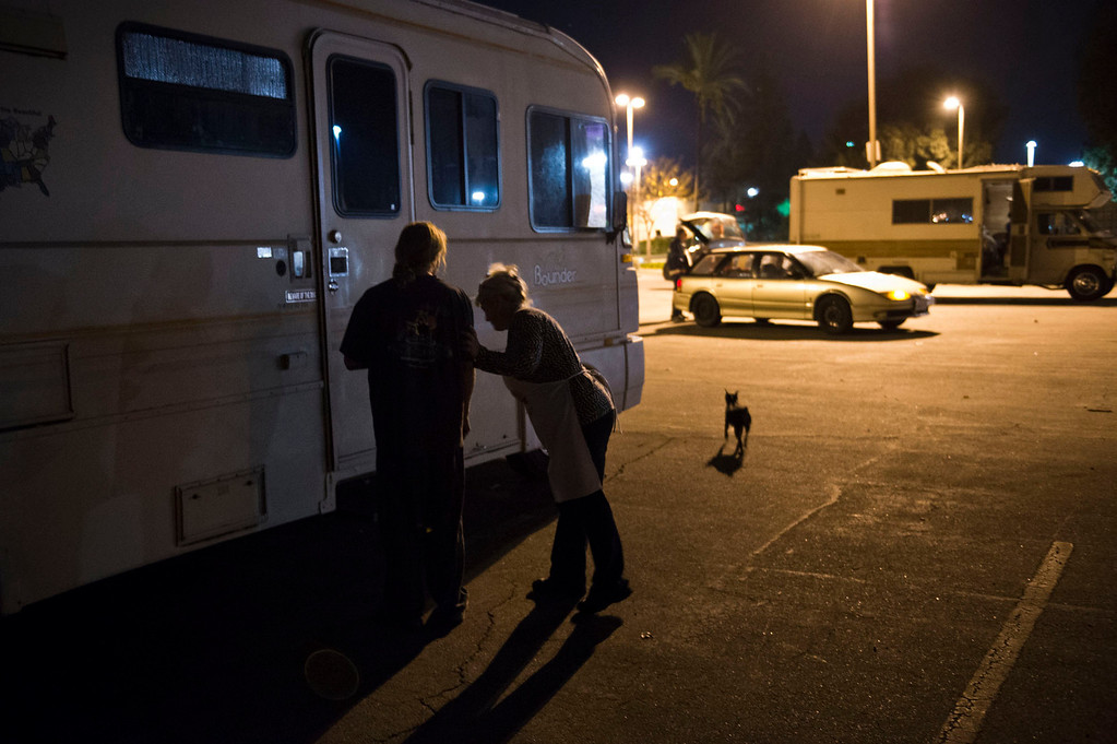 . Nicolette Wingert brings food to a homeless man who lives in his motorhome behind a department store in Covina on Wednesday night, Nov. 27, 2013. Nicolette Wingert has been feeding the homeless six days a week for the past seven years with Nurses4Christ, a nonprofit organization she founded in 2006. She and Phillip Stern of Glendora have been going every day since 2008, feeding homeless people sandwiches and hot food; giving them bottles of water, clothes and blankets. (Photo by Watchara Phomicinda/San Gabriel Valley Tribune)