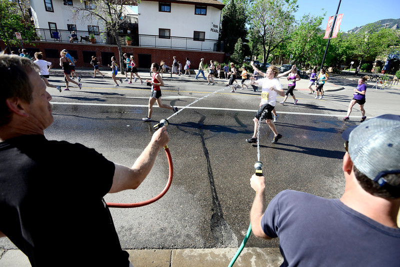 . John Severson (left) and John Koval (right) hose down Lars Zimmerman (middle) during the Bolder Boulder in Boulder, Colorado May 27, 2014.  DAILY CAMERA/Mark Leffingwell