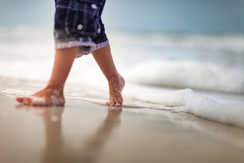 Young boy walking from the shore onto the sand.