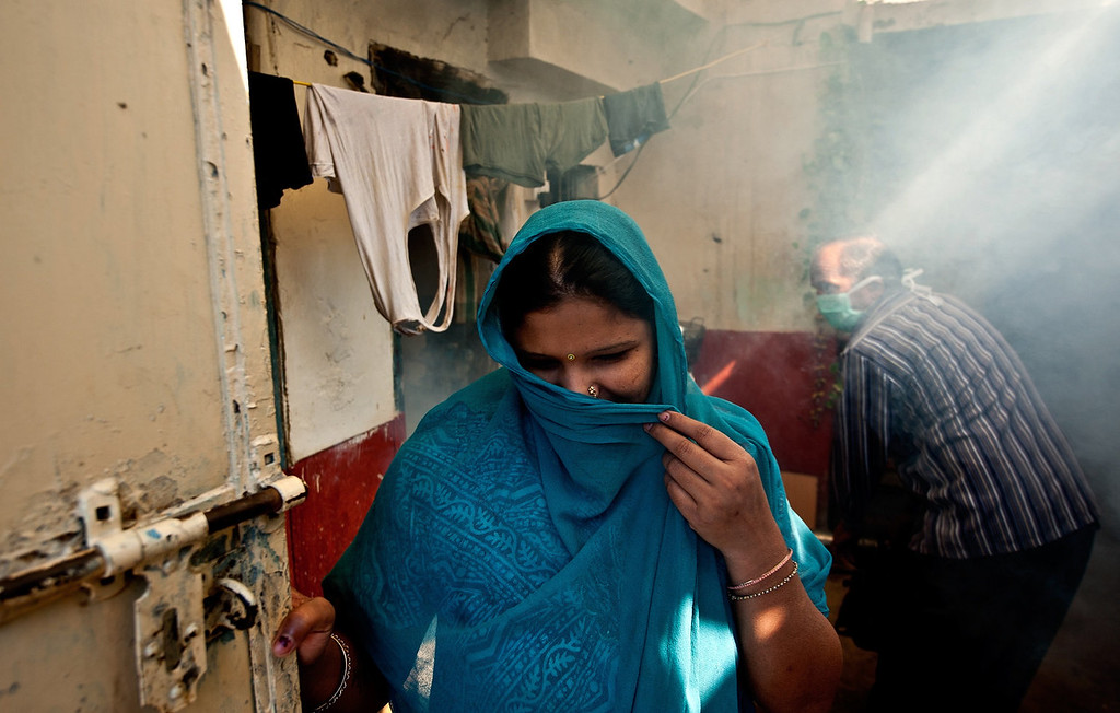 . An Indian woman covers her face from smoke as a municipal health worker (back R) fumigates against mosquitoes at a neighborhood in New Delhi on October 3, 2013. Dengue fever is a mosquito-borne disease with no known cure or vaccination that strikes fear into the citizens of New Delhi when it arrives with the monsoon rains -- just as the scorching heat of the summer is subsiding.  MANAN VATSYAYANA/AFP/Getty Images