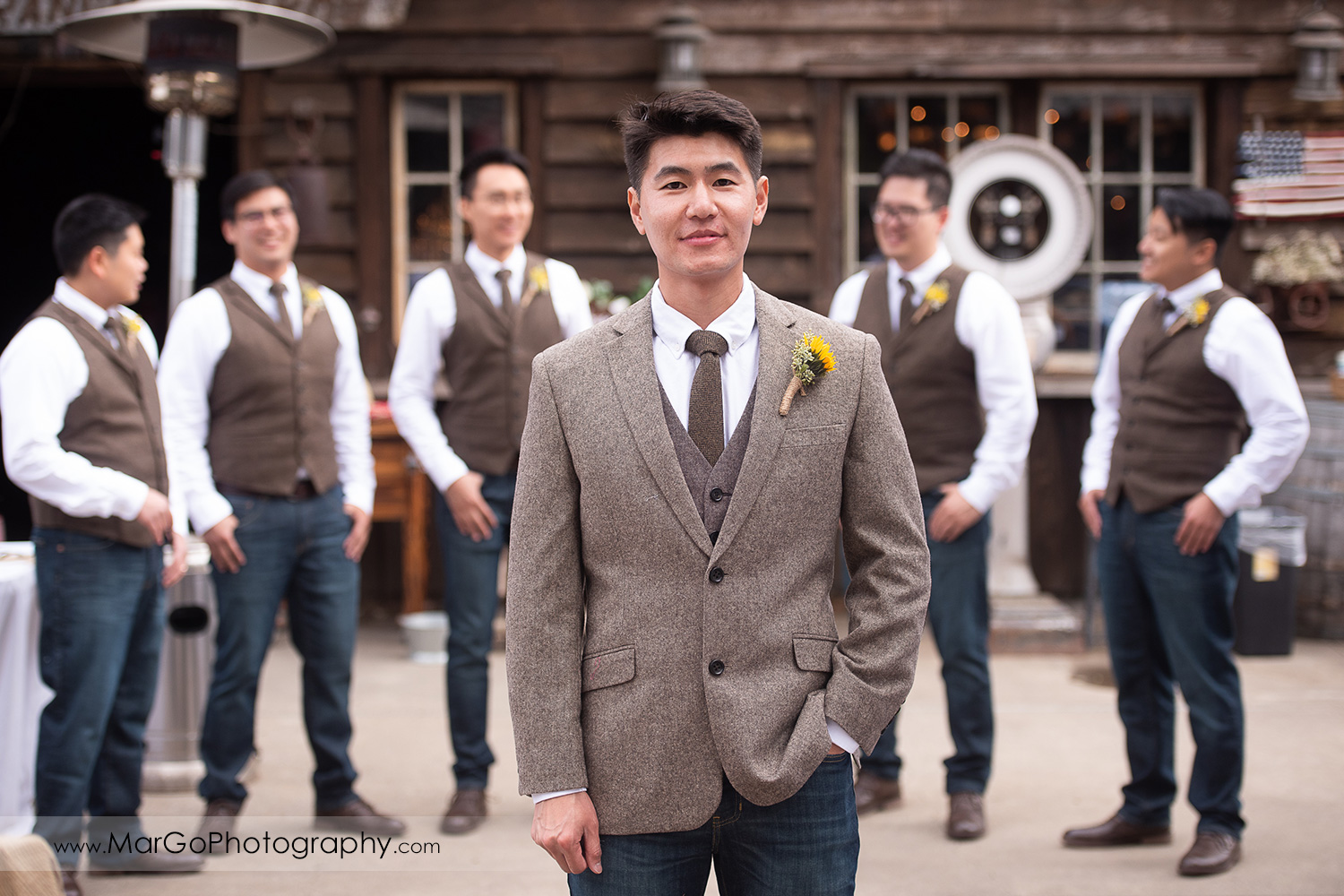 portrait of the groom with groomsmen in background at Long Branch Saloon & Farms in Half Moon Bay
