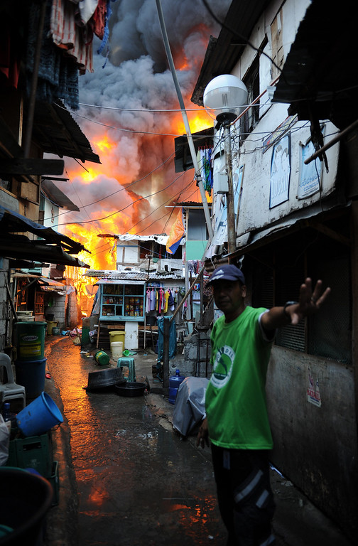 . A village watchman signals to residents to stop going near their burning houses as fire engulfs a shanty town at the financial district of Manila on July 11, 2013, leaving more than 1,000 people homeless according to city officials. There were no immediate reports of casualties from the blaze, which occurred mid-morning amid government plans to relocate thousands of families living in areas vulnerable to floods and typhoons. TED ALJIBE/AFP/Getty Images