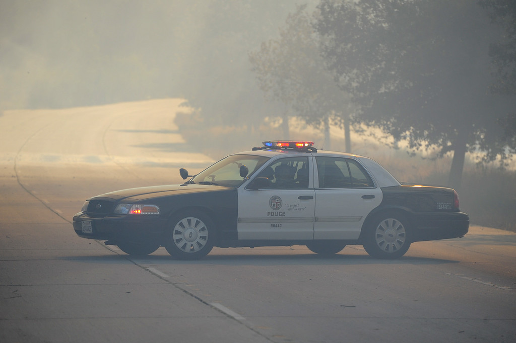. LAPD patrols along Burbank Boulevard during a brushfire in the Sepúlveda Basin, Friday, August 22, 2014. (Photo by Michael Owen Baker/Los Angeles Daily News)