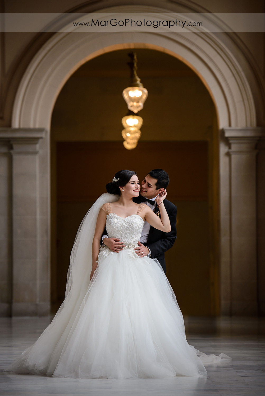 portrait of bride and groom on the forth floor of San Francisco City Hall