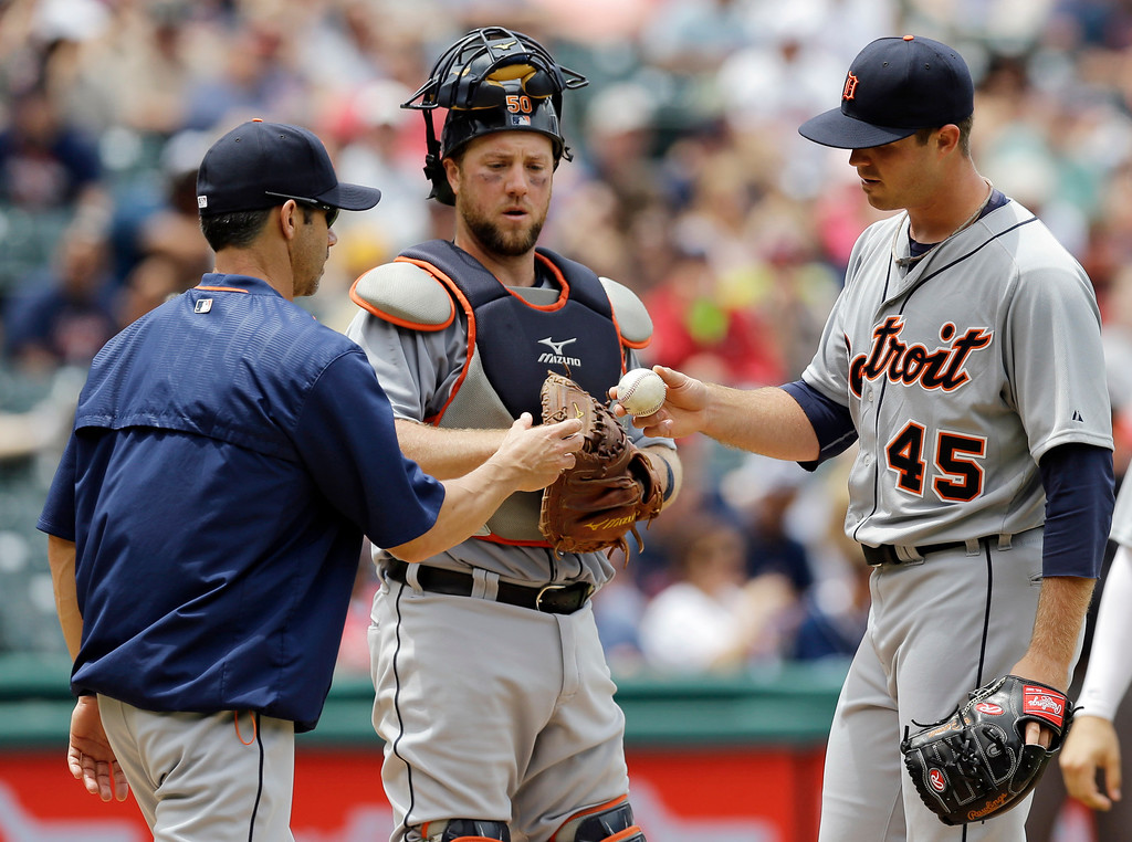 . Detroit Tigers starting pitcher Buck Farmer, right, hands the ball to manager Brad Ausmus, left, as catcher Bryan Holaday watches in the sixth inning of a baseball game against the Cleveland Indians, Wednesday, June 24, 2015, in Cleveland. Farmer pitched 5 and a third innings, giving up eight hits and five runs. The Indians won 8-2. (AP Photo/Tony Dejak)