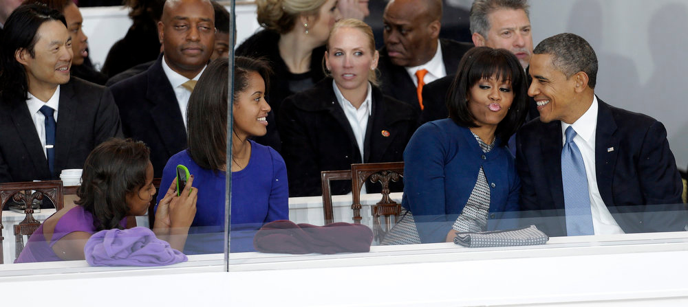 Description of . President Barack Obama and first lady Michelle Obama gesture with their daughters Sasha, left, and Malia, second from left, during the inaugural parade, Monday, Jan. 21, 2013, in Washington. Thousands  marched during the 57th Presidential Inauguration parade after the ceremonial swearing-in of President Barack Obama. (AP Photo/Gerald Herbert)