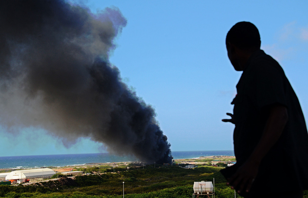 . A man looks at smoke rising in the sky after the crash of an Ethiopian military cargo which landed and burst into flames at Mogadishu airport on August 9, 2013. The plane crash resulted in the death of four of its six crew members. AFP PHOTO/MOHAMED Abdiwahab/AFP/Getty Images