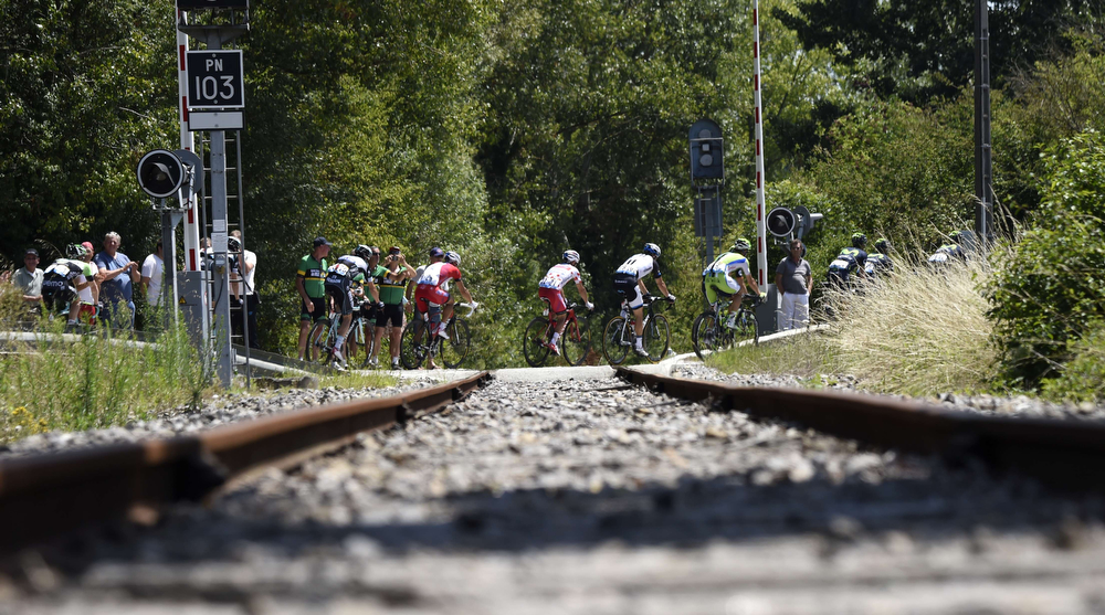 . The pack passes at a railroad crossing during the 197.5 km thirteenth stage of the 101st edition of the Tour de France cycling race on July 18, 2014 between Saint-Etienne and Chamrousse, central eastern France. (ERIC FEFERBERG/AFP/Getty Images)
