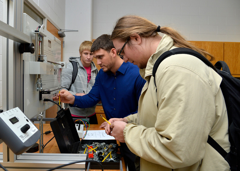 Engineering students work on a lab calculating the shear force and bending moment for evenly distributed loads on a simply supported beam.