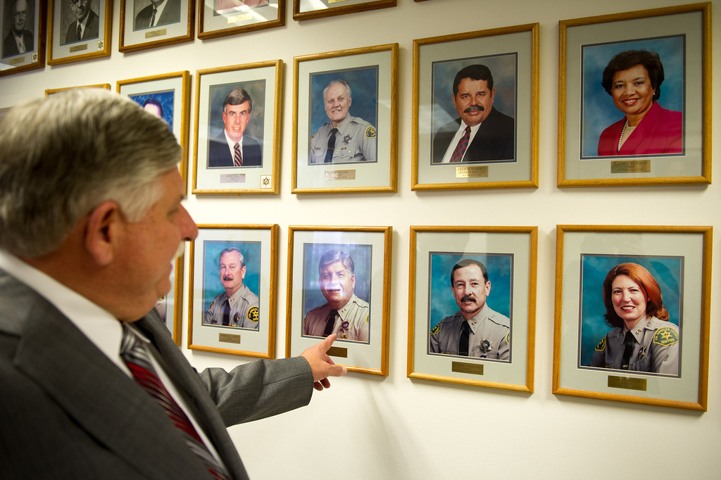 . L.A. County Interim Sheriff John Scott points out his picture among the portraits of retired chiefs and division chiefs at L.A. County Sheriff\'s headquarters in Monterey Park. Current Orange County Sheriff Sandra Hutchens is at lower right. (Photo by Michael Owen Baker/L.A. Daily News)