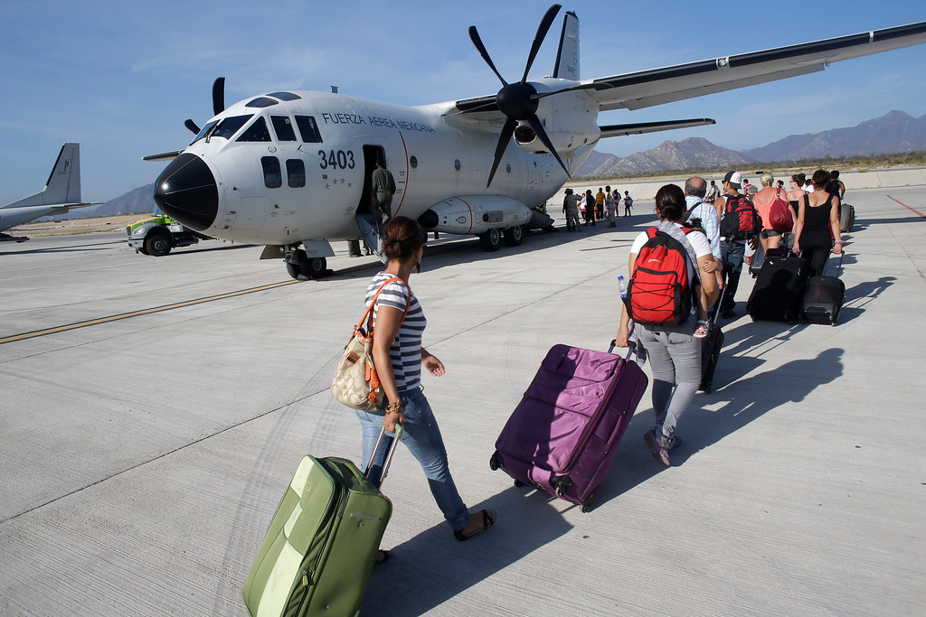 . Tourists and locals walk to a Mexican air force cargo plane which will fly them to Mexico City from Los Cabos, Mexico, Thursday, Sept. 18, 2014. Mexican authorities said 8,000 people, including tourists and locals anxious to leave, would be airlifted out on Thursday from Los Cabos following the blow from Hurricane Odile. (AP Photo/Victor R. Caivano