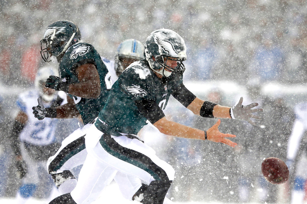 . In the snow, Philadelphia Eagles\' Nick Foles cannot hang onto the ball during the first half of an NFL football game against the Detroit Lions, Sunday, Dec. 8, 2013, in Philadelphia. (AP Photo/Michael Perez)