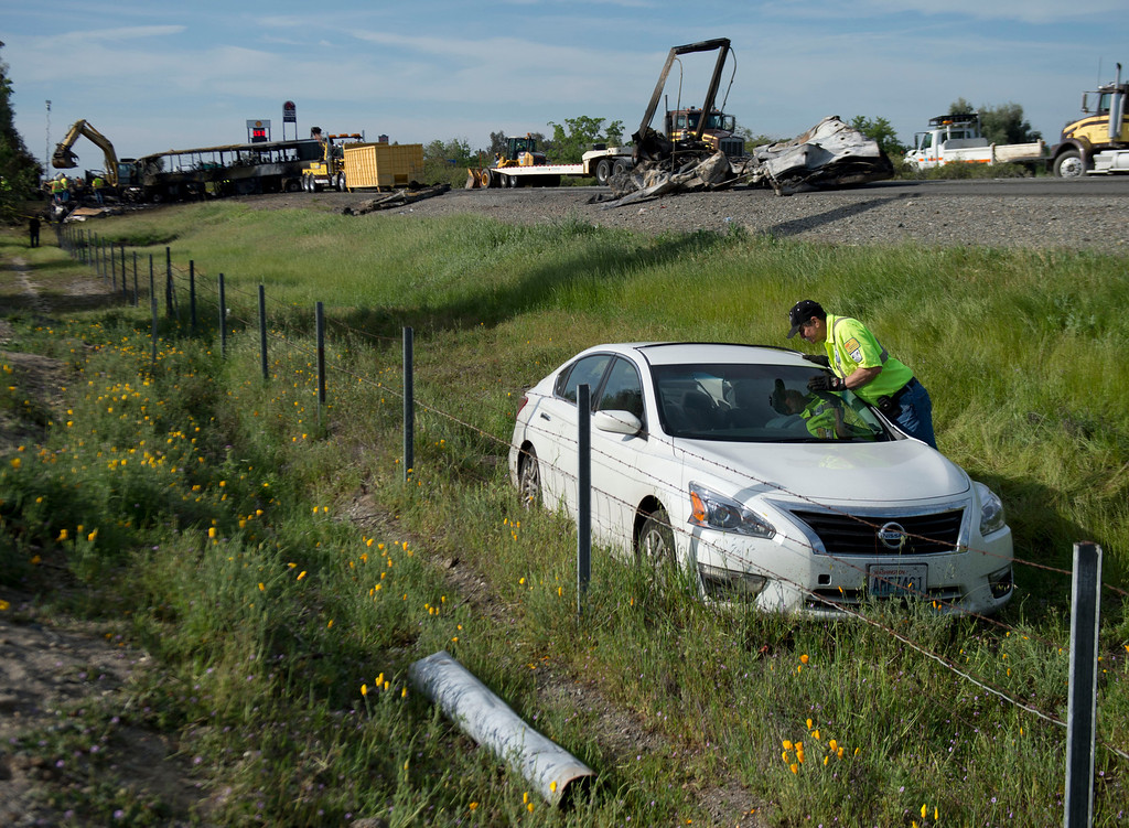 . A Nissan sedan involved in the accident of a tour bus and a FedEX truck is getting prepared to be moved on Interstate 5  in Orland, Calif, on Friday, April 11, 2014.   Ten people were killed and dozens injured in the fiery crash, Thursday, between the truck and a bus seen in background, carrying high school students on a visit to a Northern California College. (AP Photo/The Sacramento Bee, Hector Amezcua)  MAGS OUT; LOCAL TV OUT (KCRA3, KXTV10, KOVR13, KUVS19, KMAZ31, KTXL40); MANDATORY CREDIT