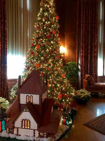 a doll house in front of a christmas tree