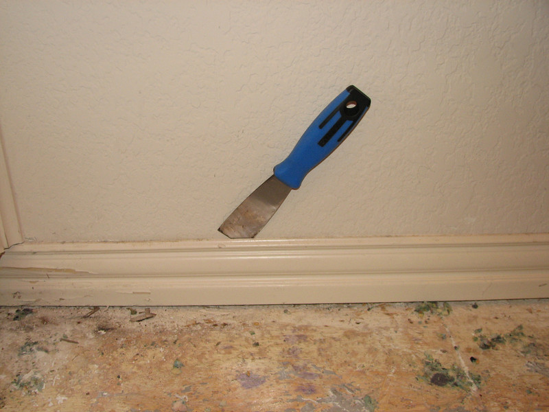 Slicing through the caulk to make removing the baseboards intact possible