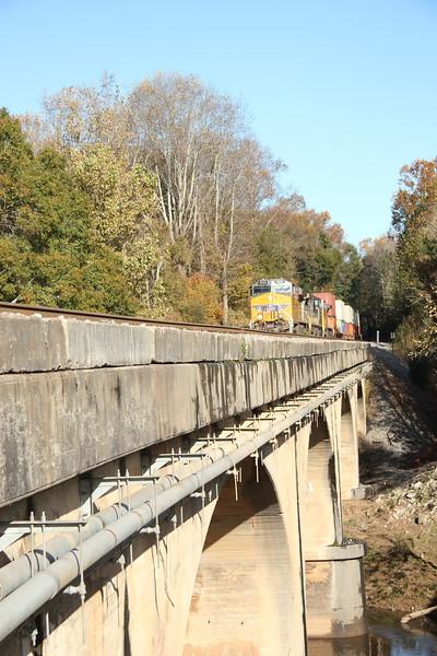 23N-06 [Intermodal; Atlanta, GA-Memphis, TN] NB UP 5532 (AC4400CTE, flag)  NS 4004 (AC44C4M, Lion's Mane Primer Fish Paint) UP 6868 (AC4400CW, flag)  86 platforms intermodal (25 international intermodal, 61 domestic doublestacks). Shot crossing Sweetwater Creek. #2 to runaround at NS Austell, Austell, GA. Since 25Q originated in Atlanta today instead of Savannah, these were back to back Atlanta-Memphis intermodals!