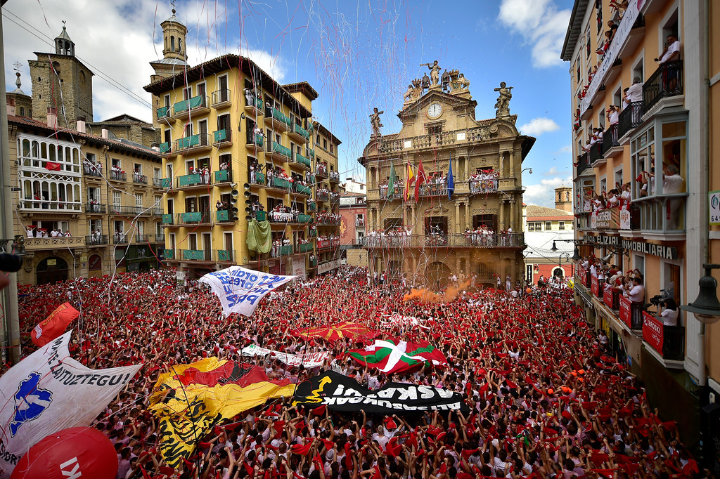 . Revellers hold up traditional red neckties during the launch of the \'Chupinazo\' rocket, to celebrate the official opening of the 2018 San Fermin fiestas with daily bull runs, bullfights, music and dancing in Pamplona, Spain, Friday July 6, 2018. (AP Photo/Alvaro Barrientos)