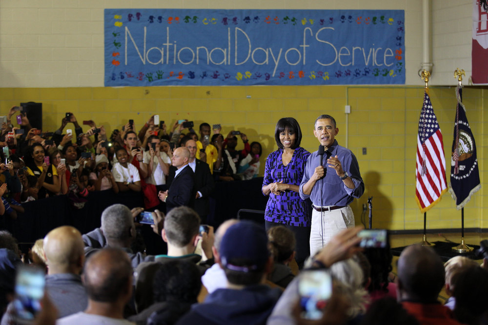 Description of . President Barack Obama (R) and first lady Michelle Obama speak to volunteers at Burrville Elementary School January 19, 2013 in Washington, DC. The event was part of the National Day of Service, the first official event of the 57th presidential inauguration weekend.  (Photo by Martin H. Simon-Pool/Getty Images)