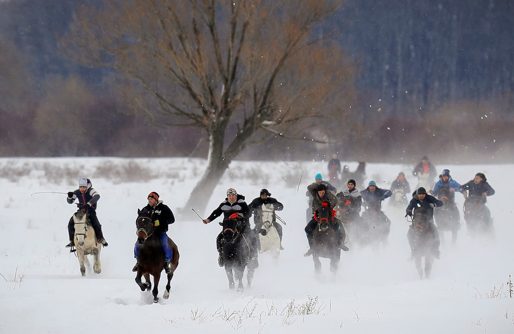 . Villagers compete in a traditional Epiphany celebration horse race in Pietrosani, Romania, Friday, Jan. 6, 2017. According to the local Epiphany traditions, following a religious service, villagers have their horses blessed with Holy water then compete in a race. (AP Photo/Vadim Ghirda)