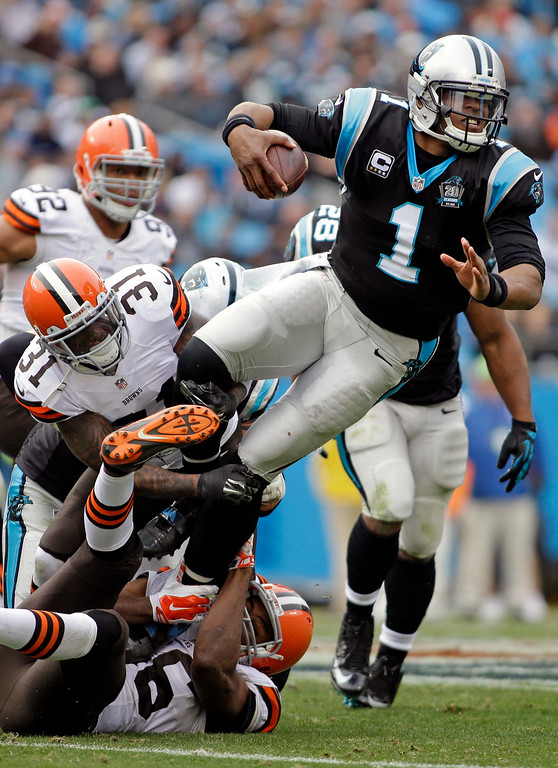. Carolina Panthers\' Cam Newton (1) is tackled by Cleveland Browns\' Donte Whitner (31) and Pierre Desir (26) in the first half of an NFL football game in Charlotte, N.C., Sunday, Dec. 21, 2014. (AP Photo/Bob Leverone)