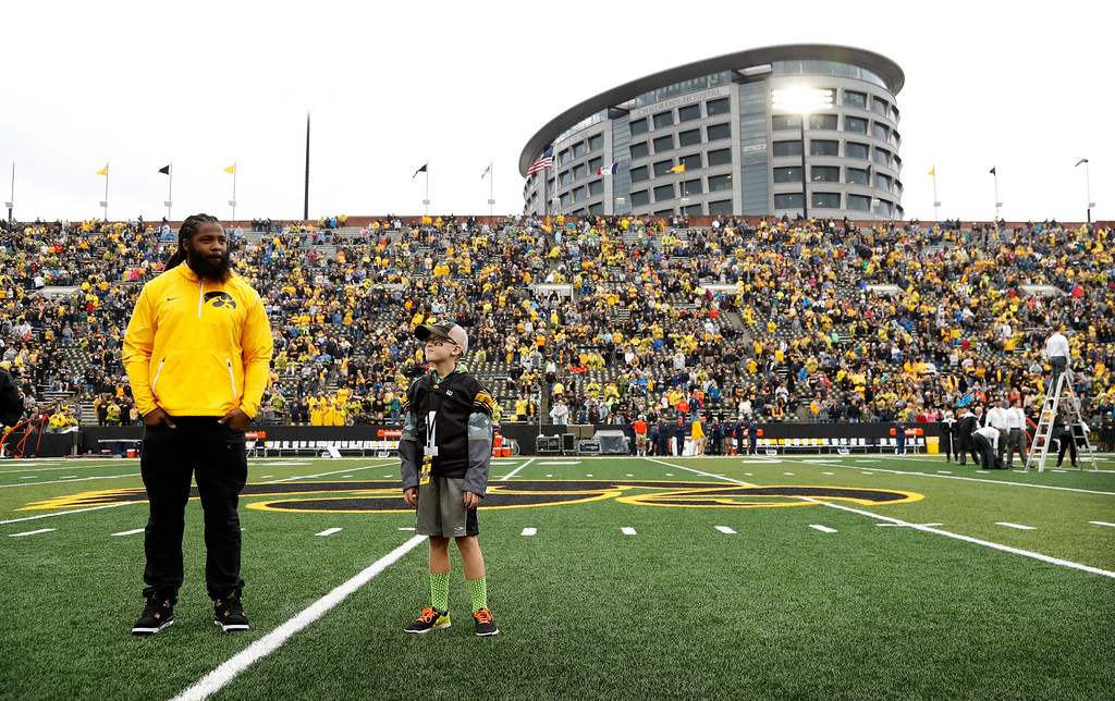 ". In this Oct. 7, 2017, photo, Atlanta Falcons defensive end and former University of Iowa player Adrian Clayborn, left, and Kid Captain Maddox Smith are honored on the field before an NCAA college football game between Iowa and Illinois in Iowa City, Iowa. ""The Wave\"" at Iowa home games, where fans salute children from the nearby hospital battling cancer and their families, has become college football\'s neatest new tradition. But it has its roots in the Hawkeyes\' \""Kid Captain\"" program, which has helped highlight kids fighting various ailments for years. (AP Photo/Charlie Neibergall)"