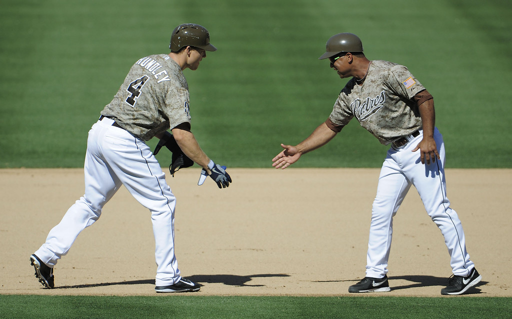 . Nick Hundley #4 of the San Diego Padres, left, is congratulated by first base coach Dave Roberts #10 after hitting a three RBI double during the seventh inning of a baseball game against the Colorado Rockies at Petco Park on September 8, 2013 in San Diego, California.  (Photo by Denis Poroy/Getty Images)