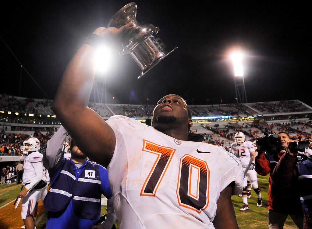 . Virginia Tech offensive guard Vinston Painter holds the Commonwealth Cup as he celebrates his team\'s 42-13 win over Virginia after an NCAA college football game at Scott Stadium in Charlottesville, Va., Saturday, Nov. 28, 2009.  (AP Photo Don Petersen)