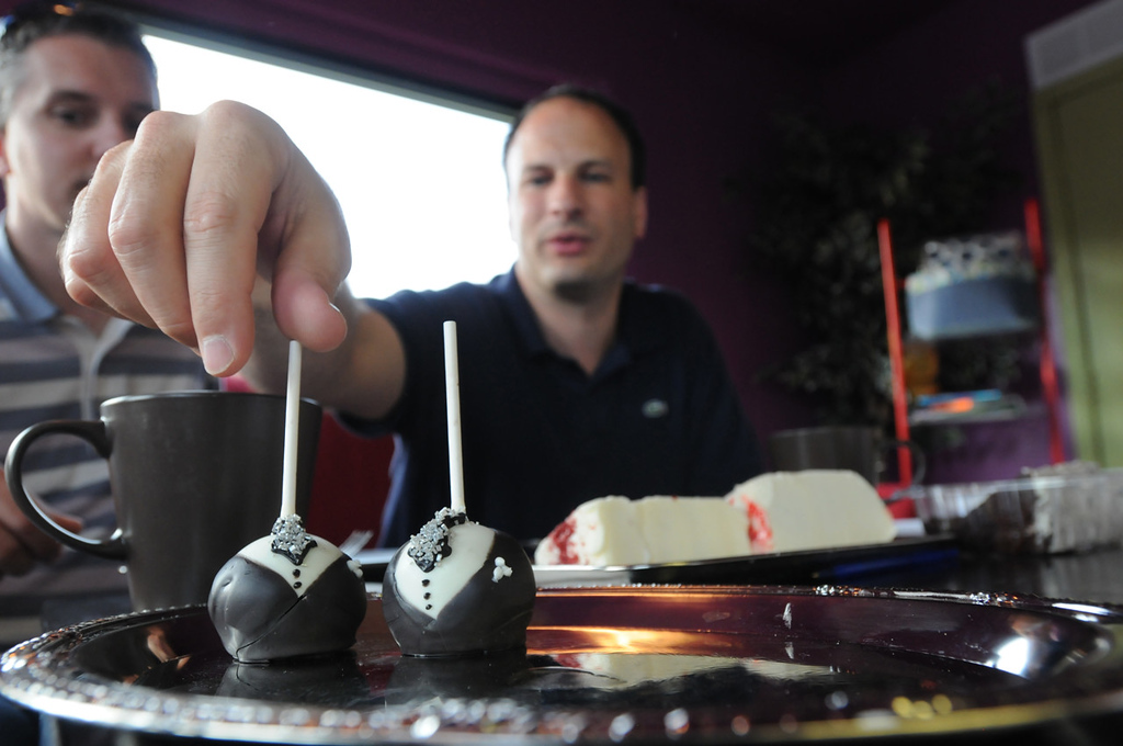 . Bradley Weber, right, checks out a tuxedo cake pop made by bakers at Taste of Love Bakery in West St. Paul, where he and Ryan Pfeifle went to make their decision on a wedding cake.  (Ginger Pinson: Pioneer Press)