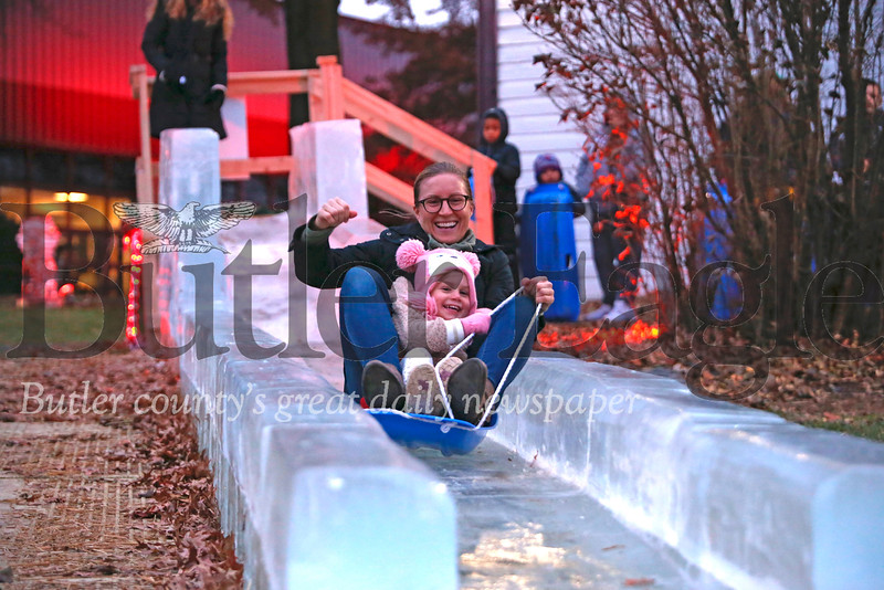 Amelia Palermo, 3, and her mom Ryanne of Mars enjoy a ride on the ice slide at Santa's First Stop Eagle North Pole Ice Festival Friday. Seb Foltz/Butler Eagle