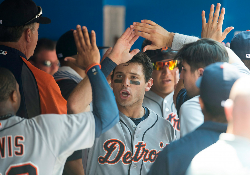 . Detroit Tigers\' Ian Kinsler, center, and Miguel Cabrera celebrate with teammates after scoring on Victor Martinez\'s two-RBI double in the sixth inning of a baseball game against the Toronto Blue Jays in Toronto on Saturday, Aug. 9, 2014.  (AP Photo/The Canadian Press, Darren Calabrese)