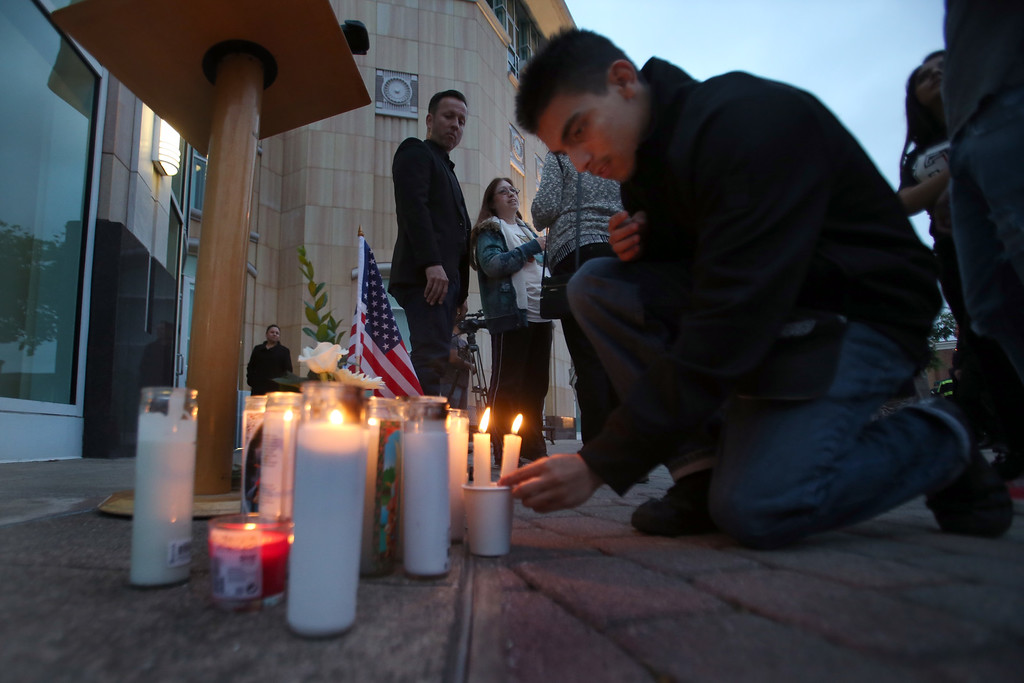 . Alejandro Reyes, 18, of Hayward, sets a candle in place at the end of a vigil for slain Hayward police Sgt. Scott Lunger at Hayward City Hall in Hayward, Calif., on Wednesday, July 22, 2015. Lunger was killed during a traffic stop early Wednesday. (Ray Chavez/Bay Area News Group)