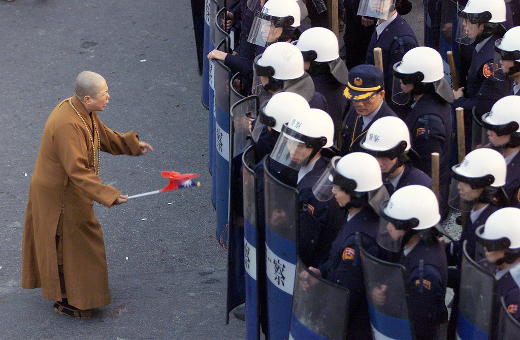 . A Buddhist nun holding a Taiwanese flag confronts riot police outside the Nationalist Party headquarters in Taipei March 20, 2000. Hundreds of protesters demanded the resignation of party chairman Lee Teng-hui after presidential elections ended more than five decades of Nationalist rule. Bobby Yip / Reuters