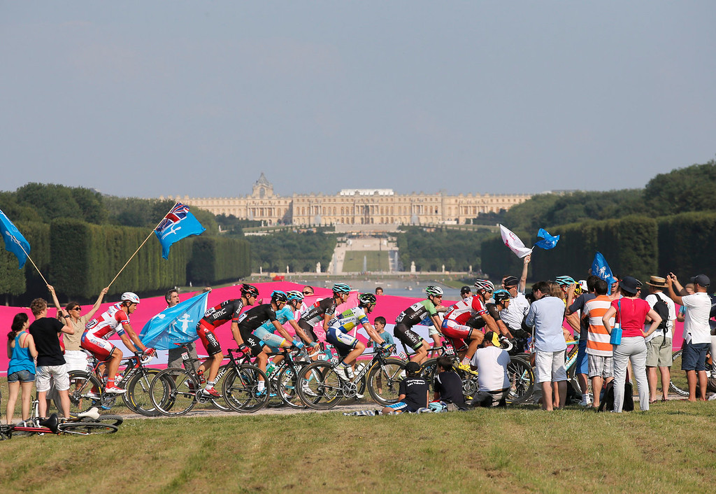 . The packs with Tejay van Garderen of the U.S., second rider from the left, rides through the gardens of the Versailles castle, seen behind, as anti-gay marriage activists wave flags during the 21st and last stage of the 100th edition of the Tour de France cycling race over 133.5 kilometers (83.4 miles) with start in Versailles and finish in Paris, France, Sunday July 21 2013. (AP Photo/Christophe Ena)