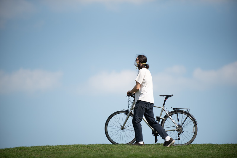 West Humboldt Park resident Andrew Tham wears an N-95 mask and walks a bicycle in Humboldt Park as temperatures reached 80 degrees Fahrenheit in parts of Chicago while cases of Coronavirus in Illinois continue to rise on Tuesday, April 7, 2020. | Colin Boyle/Block Club Chicago